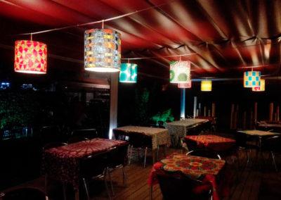 Pantallas cilíndricas con estampado en telas con diversos diseños para terraza de restaurante de Artesanía Antonio